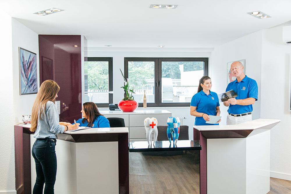 Zahnarzt Köln Innenstadt - Dr. Bongartz und zwei mitarbeiterinnen arbeitem am Empfang unserer Praxis