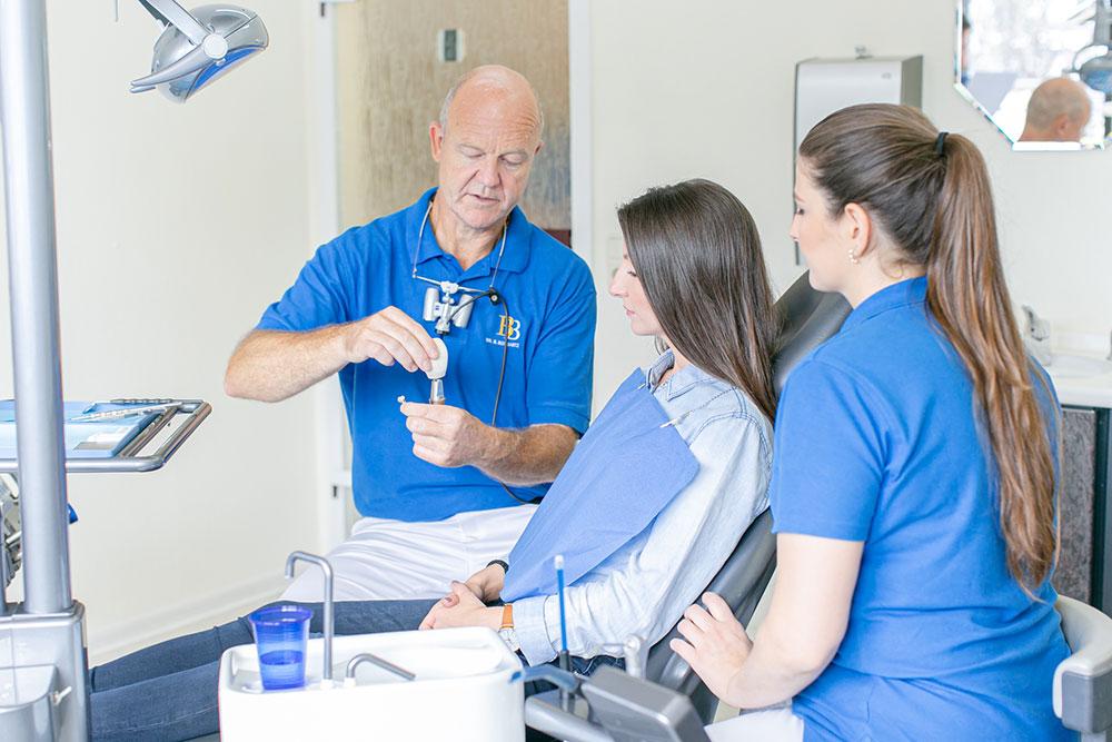 Zahnarzt Köln Innenstadt - Dr. Bongartz erklärt Patientin auf Zahnarztstuhl, wie ein Implantat funktioniert